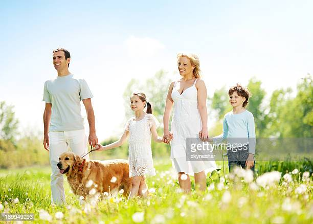 Happy family walking their dog in a park.