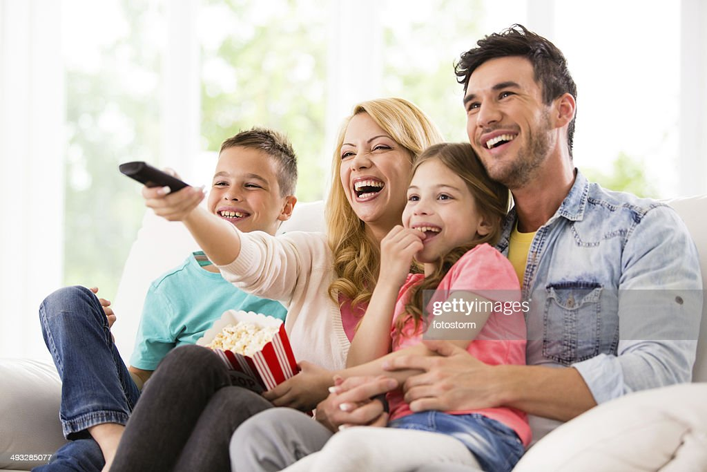 Happy family watching TV and eating popcorn : Stock Photo