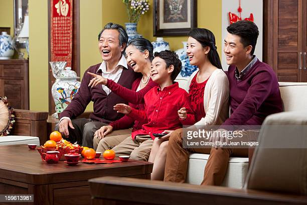 Happy family watching TV during Chinese New Year