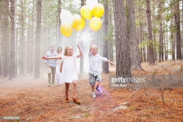 Famiglia felice con palloncini nel bosco