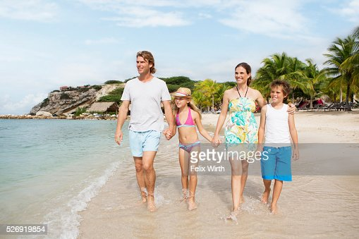 Happy family with children (10-12) walking along beach : Foto stock