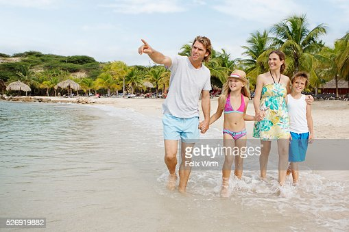Happy family with children (10-12) walking along beach : Foto de stock