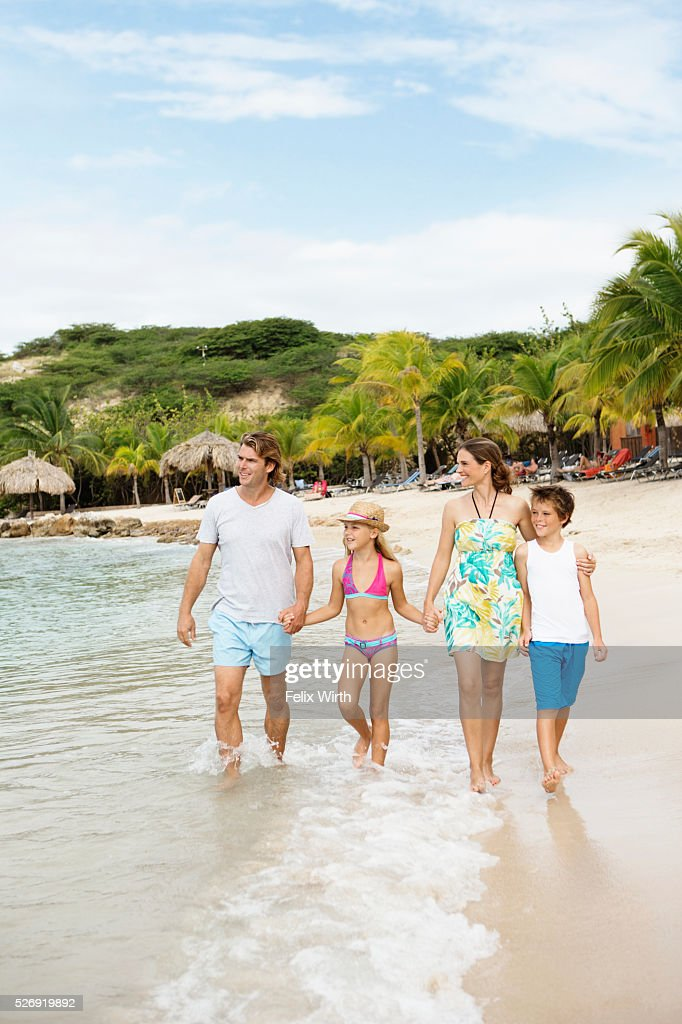 Happy family with children (10-12) walking along beach : Stockfoto