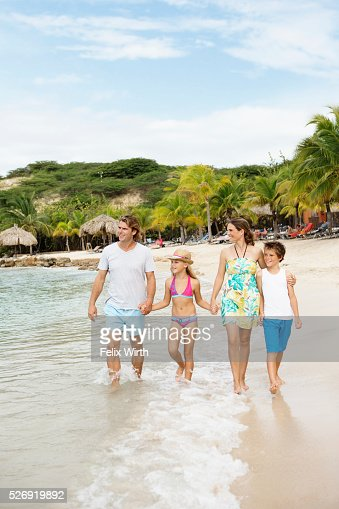 Happy family with children (10-12) walking along beach : Stock Photo