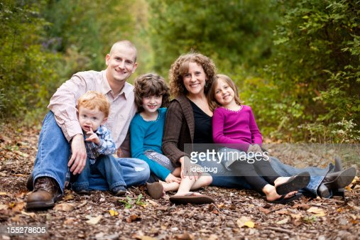 Happy Family with Father, Mother, Daughters and Son in Woods