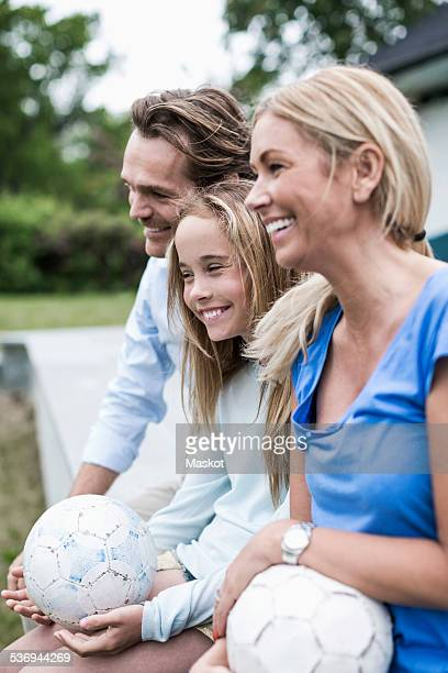 Happy family with footballs sitting at porch
