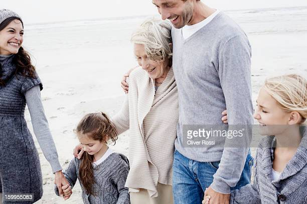Happy family with grandmother walking on the beach