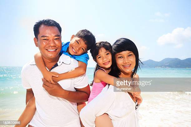 Happy family with kids on the beach.