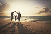 silhouette of family with two kids on play on sunset beach