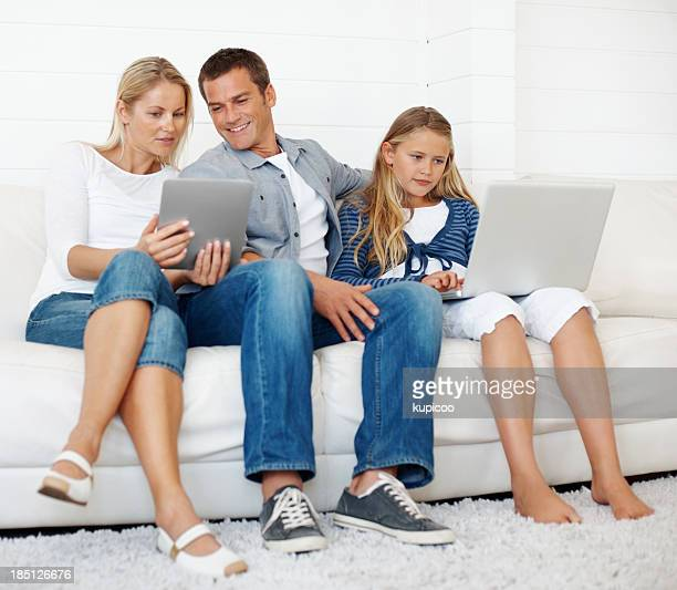 Happy family with laptop and tablet PC