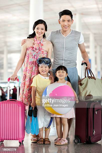 Happy family with luggage at the airport