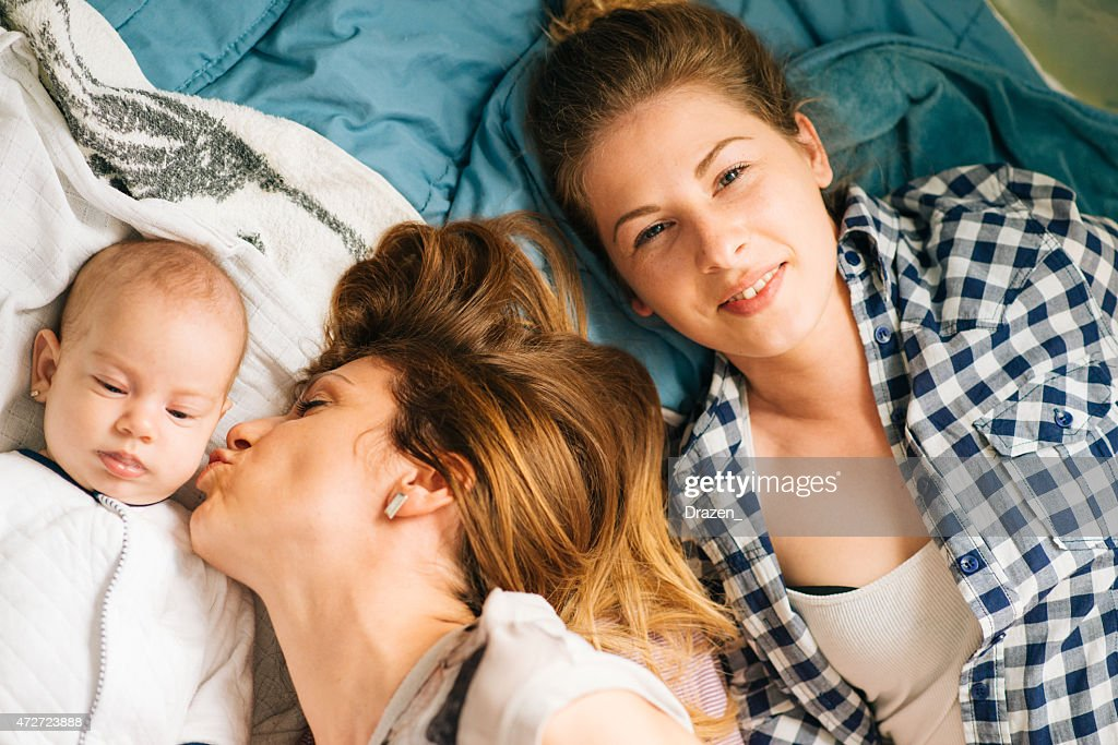 Happy family with mother, baby and aunt lying on bed