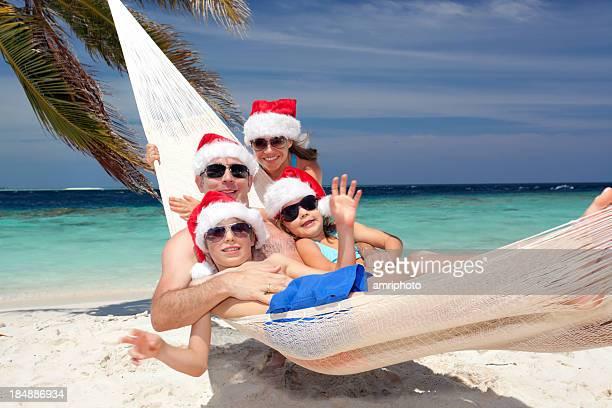 Famille heureuse avec des chapeaux de Père Noël dans un hamac
