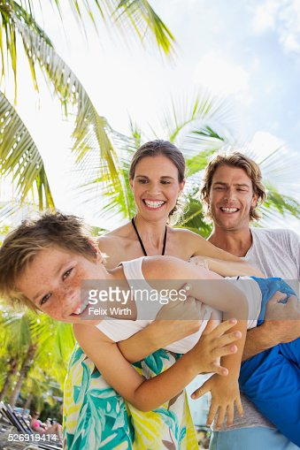 Happy family with son (10-12) embracing and hugging on beach : Stockfoto