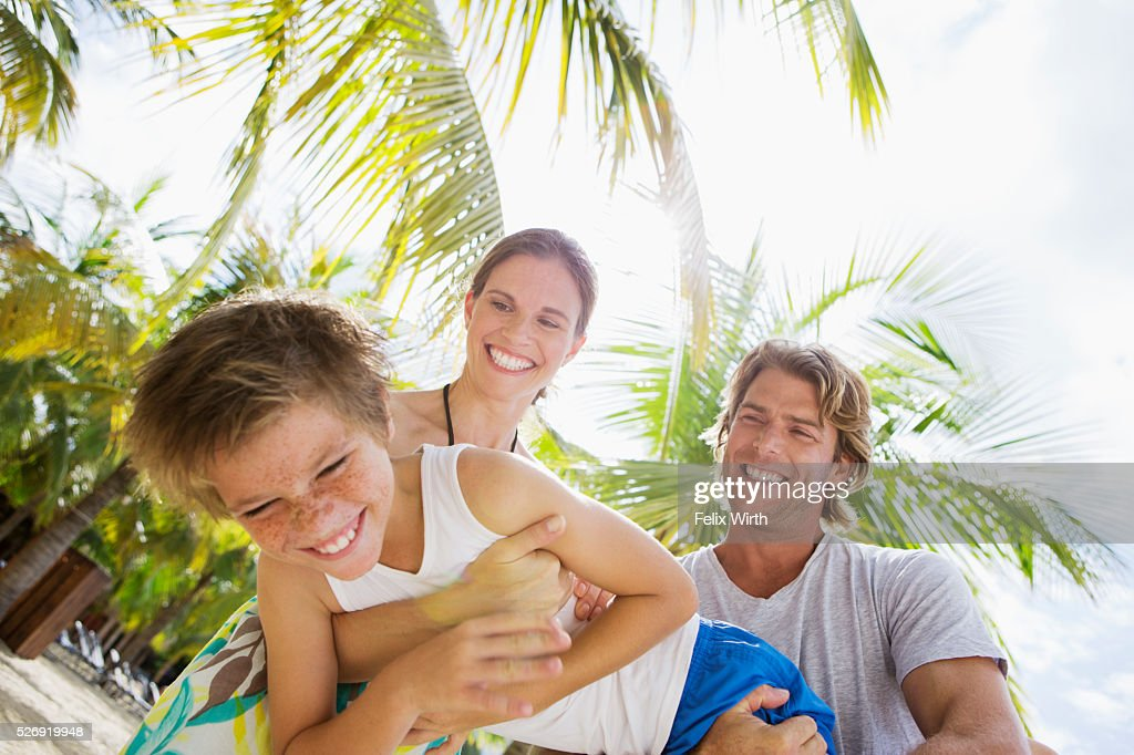Happy family with son (10-12) embracing and hugging on beach : Foto stock