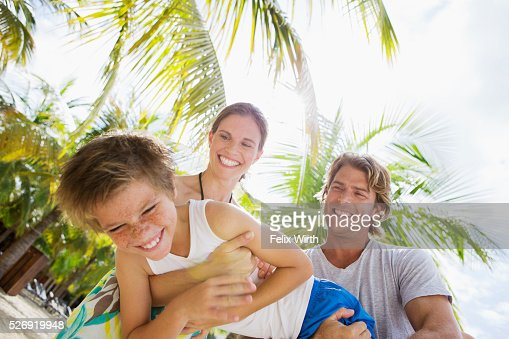 Happy family with son (10-12) embracing and hugging on beach : Stock-Foto