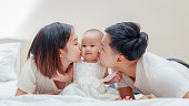 Happy family, Young Asian father and mother kissing their baby girl on the bedroom