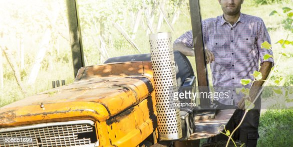 Happy farmer with his tractor : Stock Photo