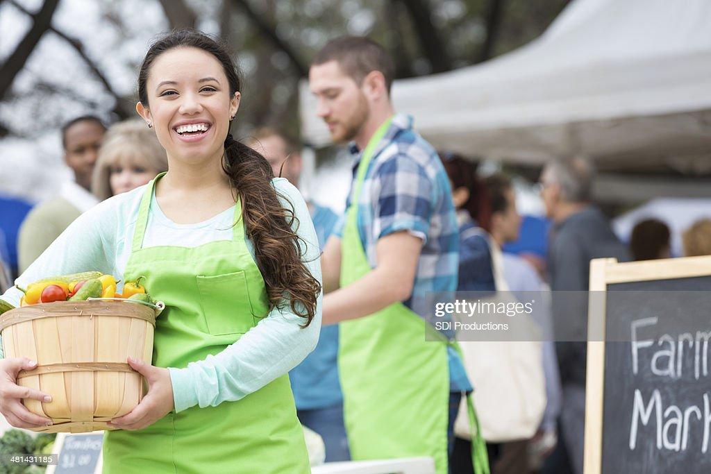 Happy farmers market vendor holding basket of fresh vegetables