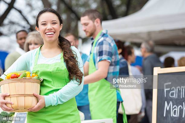 Happy farmers market vendor holding basket of fresh vegetables