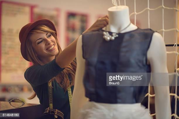 Glücklich Modedesigner Kleidung auf einer Schaufensterpuppe anpassen.