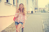 Happy Fashion Woman in the City Street. Smiling Trendy Girl in Summer. Toned Photo with Copy Space.