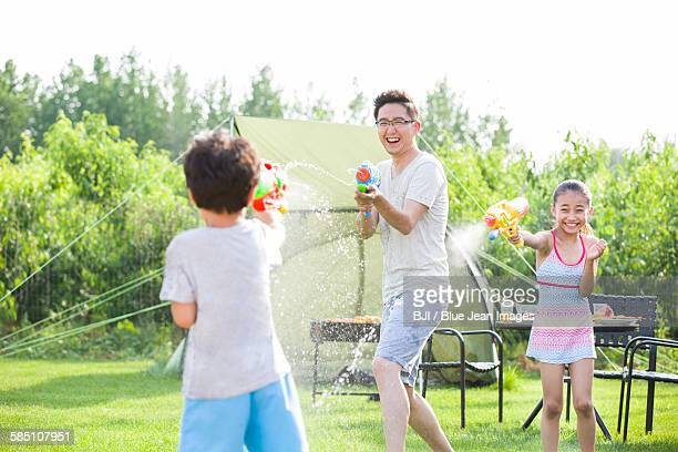 Happy father and children playing squirt guns