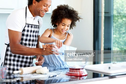 Happy father and daughter preparing food : Stock Photo