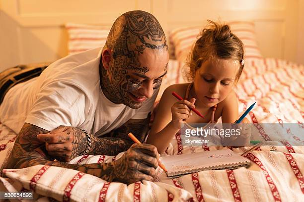 Happy father and daughter sketching on the paper in bedroom.