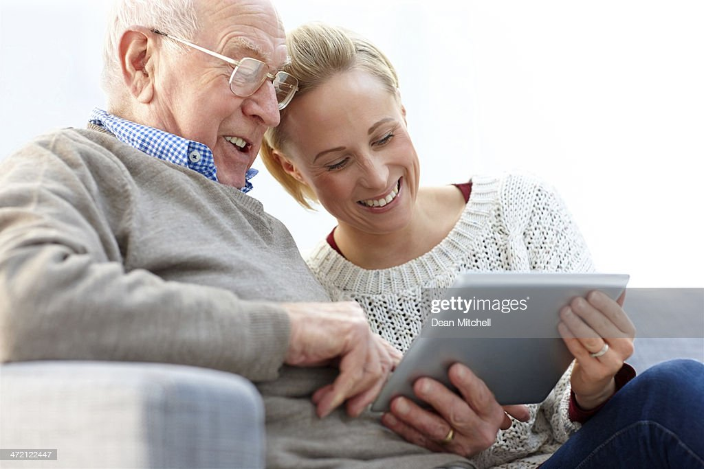 Happy father and daughter using digital tablet at home : Stock Photo
