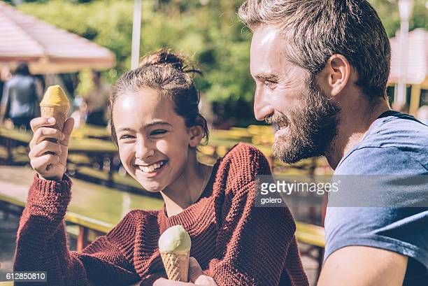happy father and his daughter eating ice cream outdoors