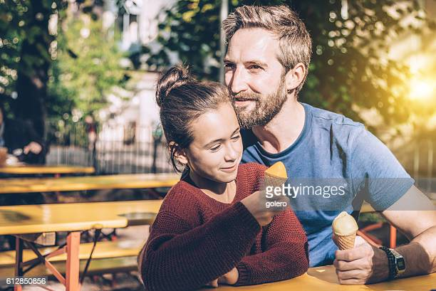 happy father and smiling daughter eating ice cream outdoors
