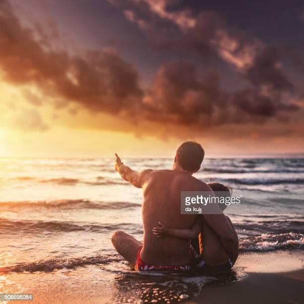 Heureux père et fils, appréciant la mer au coucher du soleil
