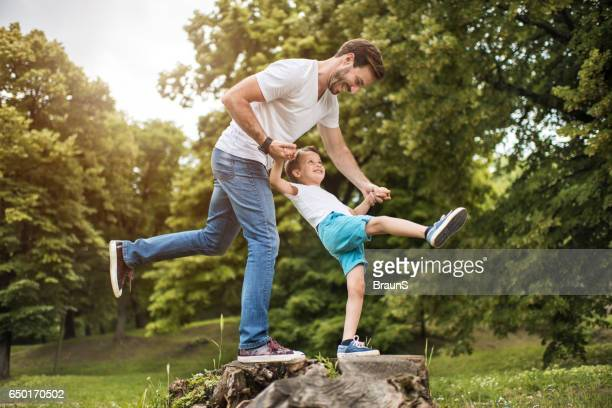 Happy father and son having fun in the park.