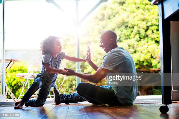 Happy father and son playing on floor at home