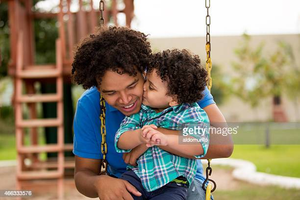 Happy father and son playing on swing