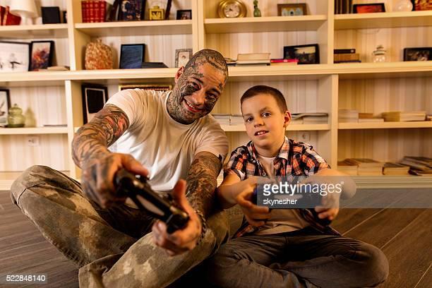 Glückliche Vater und Sohn spielen Videospiele spielen zusammen.