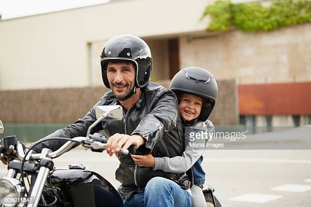 Happy father and son riding motorbike