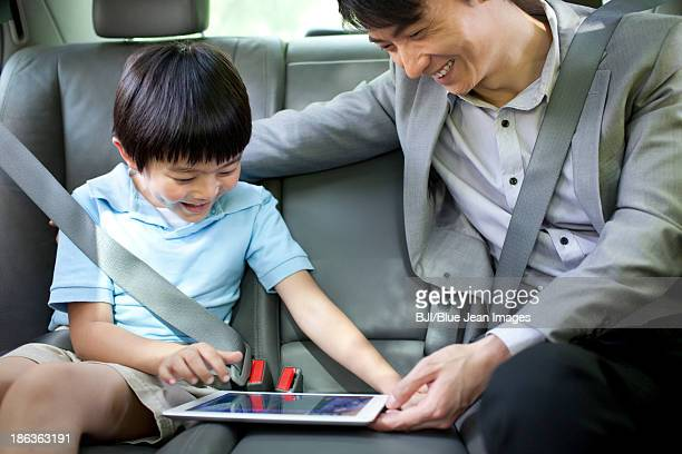 Happy father and son with digital tablet in car