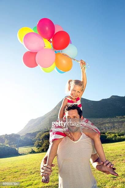 Happy father carrying daughter with balloons on shoulders
