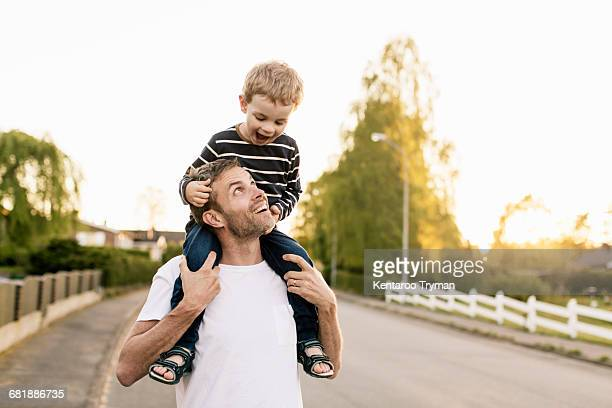 Happy father carrying son on shoulders while standing at street against clear sky