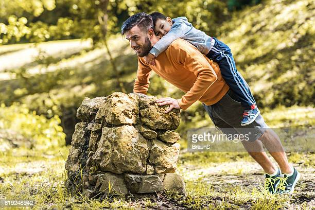 Happy father doing push-ups with his little boy in nature.
