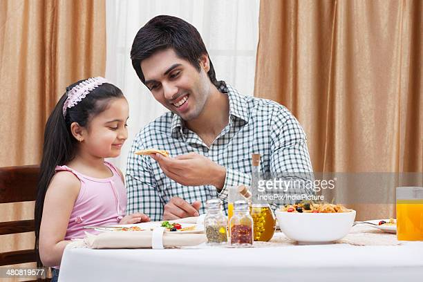 Happy father feeding cute daughter piece of pizza at restaurant table