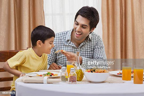 Happy father feeding piece of pizza to son at restaurant table