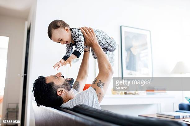 Happy father lifting daughter while sitting on sofa at home