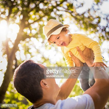 Happy father lifting his laughing little girl playfully