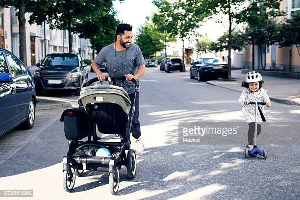 Happy father looking at girl riding push scooter on street in city