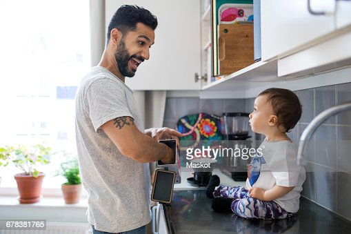 Happy father making breakfast while looking at toddler sitting on kitchen counter