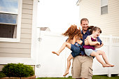 Happy Father Playing With His Daughters Outdoors in Their Yard