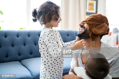 Happy father wearing cap playing with children in living room